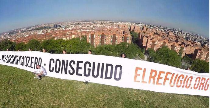 Voluntarios de El Refugio desplegando ayer la pancarta de 30 m2 con Madrid de fondo