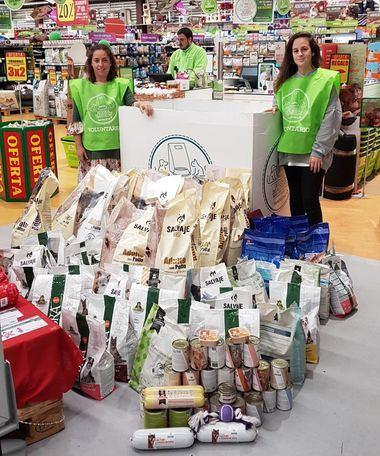 Voluntarios junto a los productos donados durante la campaña en uno de los locales de Tiendanimal.